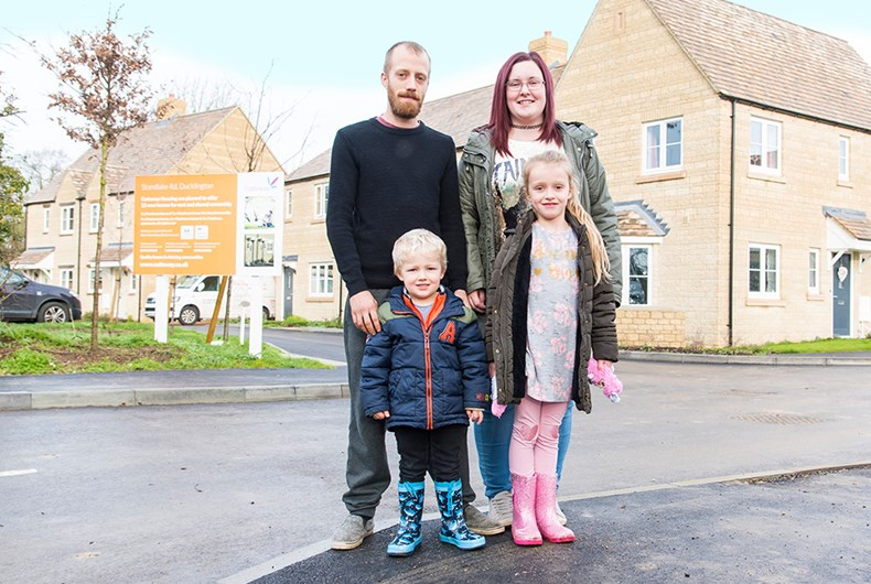 Family of four stood outside their new home