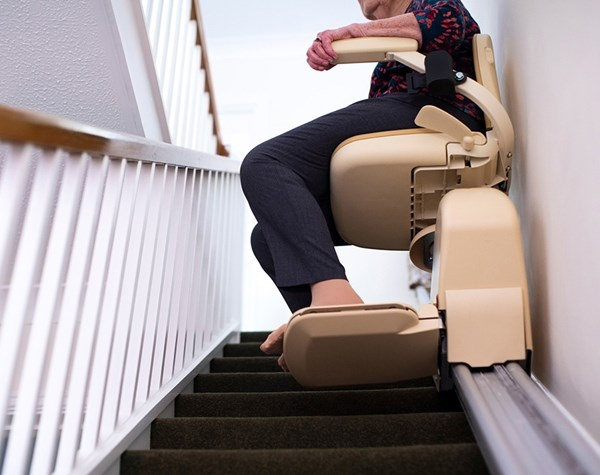 Lady using a stairlift in her home