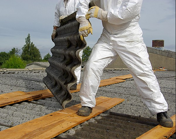People wearing protective clothing working on asbestos roof