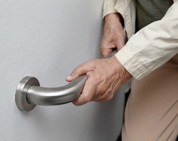 Elderly lady holding hand rail